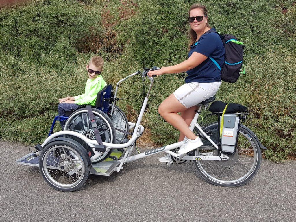 rolstoelfiets met rolstoel erop en begeleider fietst